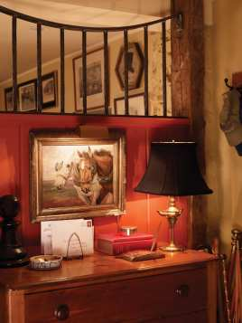 The former garage gets an English hunt country treatment with horse stalls, red walls and the children'€™s trophies on display.