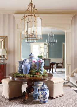 The gracious foyer includes nickel-studded ottomans and classic porcelain.