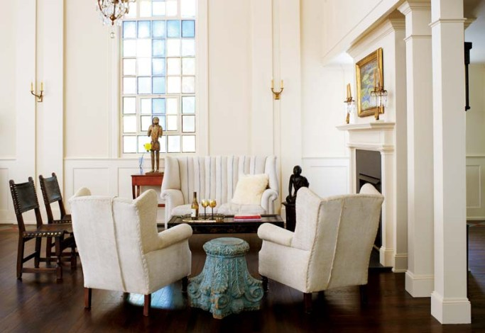 A collection of furniture covered in vintage linen provides a cozy spot by the fireplace.