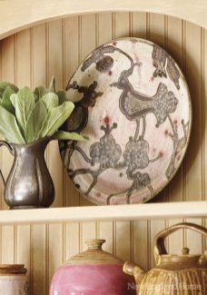 A plate by potter Lala Howard holds a place of honor on the top shelf.
