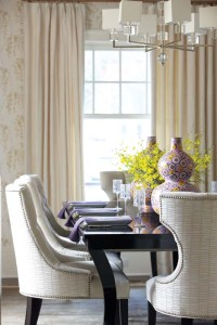 Textured linen chairs and a black lacquered table are a sophisticated mix in the dining room.