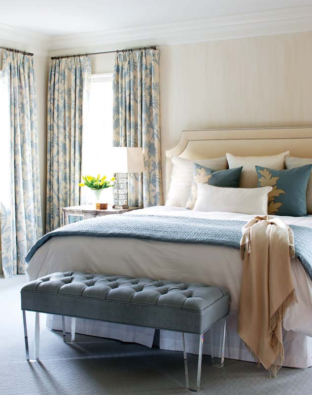 Traditional and modern mix in the master bedroom, where a Lucite-legged bench keeps company with aged, silvered nightstands.
