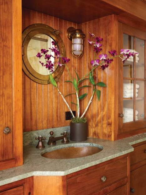 A downstairs bathroom takes on the feel of a shipboard head with its floor-to-ceiling paneling.