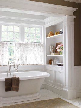 The master bath tub sits in a nook with views of a pond.