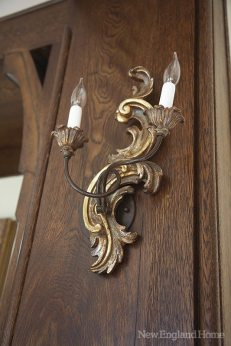 The gilt on a hand-carved Italian sconce gleams against the restored woodwork.