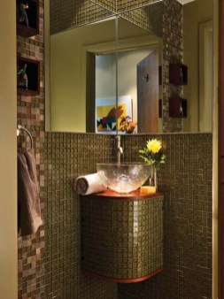 A corner mirror and a sink base tiled to match the walls make a tiny powder room seem larger