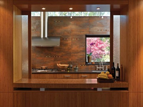 The kitchen tiles gleam with a finish of recycled aluminum and copper and inset strips of colored glass