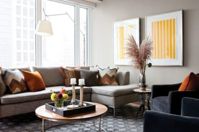 The designers used pale walls to let the view take center stage, then grounded the living room with a graphic rug and comfortable furniture in earthy colors.
