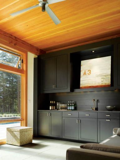 In the kitchenette, black cabinets frame a painting by Keith Wagner