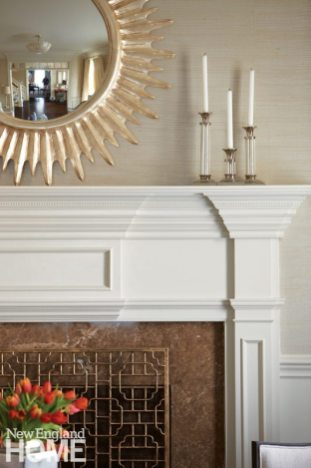 The mix of traditional and modern continues at the fireplace, where the pretty millwork pops against the sisal wallcovering.