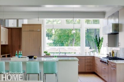 Kitchen designer Donna Venegas kept the open kitchen streamlined and neat by relegating some of the everyday food preparation equipment to a pantry area to the left of the island. The only visible appliances are the range top and its good-looking zinc hood.