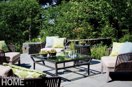 A stone terrace sits on the east side of the house. Stone steps link the upper terrace with the backyard playing field.