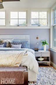 Soft, organic textiles heighten the warmth of the master bedroom, which is tucked under one of the house's flat-roofed dormers.