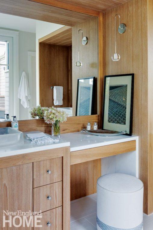 The same marble tops the bleached teak vanity.