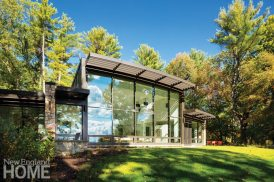A Merz Construction home in Massachusetts embraces its riverside view via an expansive glass wall.