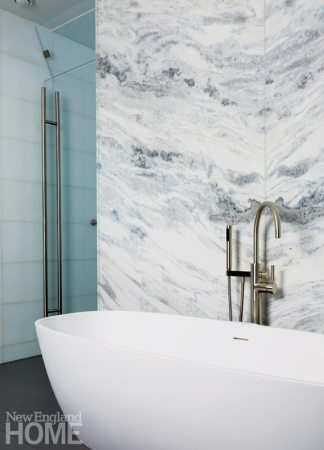 Freestanding bathtub with marble wall