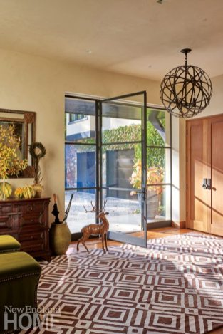 An oversize glass door lets lots of light into the foyer, where a deer statue stands as a reminder of the homeowners' intent to blend the outdoor environment with the indoors.
