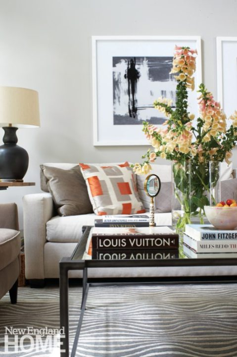 Homeowner and designer Nancy Monahan began with a calm palette of pale gray. Here in the great room, splashes of orange add a lively touch.