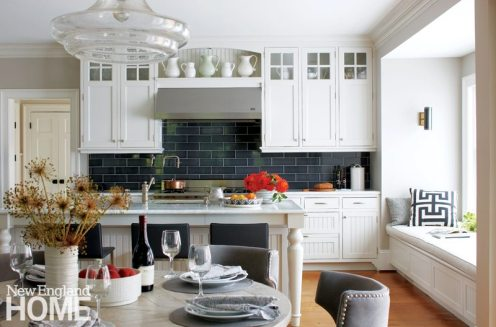 The mostly white kitchen is enriched by the graphite gray of the backsplash tile and counter stools. Casual dinners are often staged at the custom table from Parc Home.