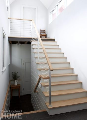 In the mudroom and back stairway, shiplap paneling and cable rails carry over themes from the rest of the house.