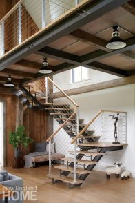 With reclaimed barnwood treads, a steel carriage, and cable railings, the great great room staircase captures the home's integration of old and new.