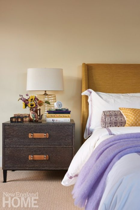 A custom headboard in gold fabric by Pierre Frey plays well with the yellow and purple bedclothes.