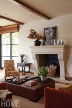 Open ceiling beams and a leather-clad ottoman add a hint of rich rusticity. A limestone Chesneys Marseilles mantel evokes eighteenth-century French Provincial design; the roman shades can be dropped to create intimacy around a merry fire.