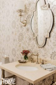 The designer used wallpaper in all of the smaller spaces for impact, including this Thibaut paper with a touch of metallic in the powder room.