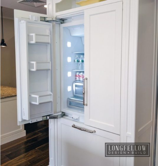 Custom cabinetry masterfully conceals the refrigerator.