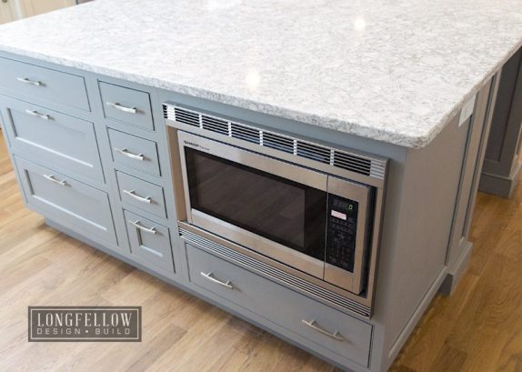 Kitchen islands have become a favored spot for tucking microwaves out of sight.