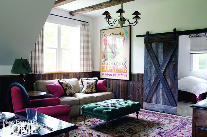 A sliding door fabricated from reclaimed barn wood cordons off the bedroom from the New England-inspired living room.