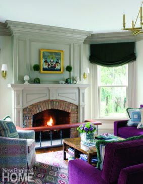 A plum-colored sectional invites lounging by the fire in the family room.