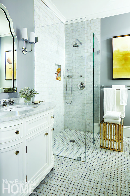 The master bath is all practical simplicity and beautiful light. Brass fixtures from the Astor collection by Newport Brass and a handsome brass slat bench provide a bit of contrast to all the Carrara marble.