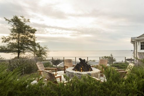 Situated above a pool house and grotto, this elevated firepit creates a sense of privacy while overlooking expansive views of Long Island Sound. Photography by Neil Landino