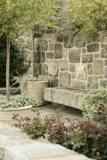 Evoking the rocky coastline, the entry courtyard for this waterfront residence employs salvaged granite curbing and locally sourced stone veneer to create a bold connection to the site. Walkways and niches abound and create human scale and interest, with slab stone benches, containers, and sourced garden antiques to compliment the timeless setting. Photography by Neil Landino