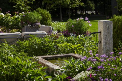 This reclaimed granite post and handcrafted custom granite trough create a unique water feature that compliment this agrarian site. Photography by Anthony Crisafulli