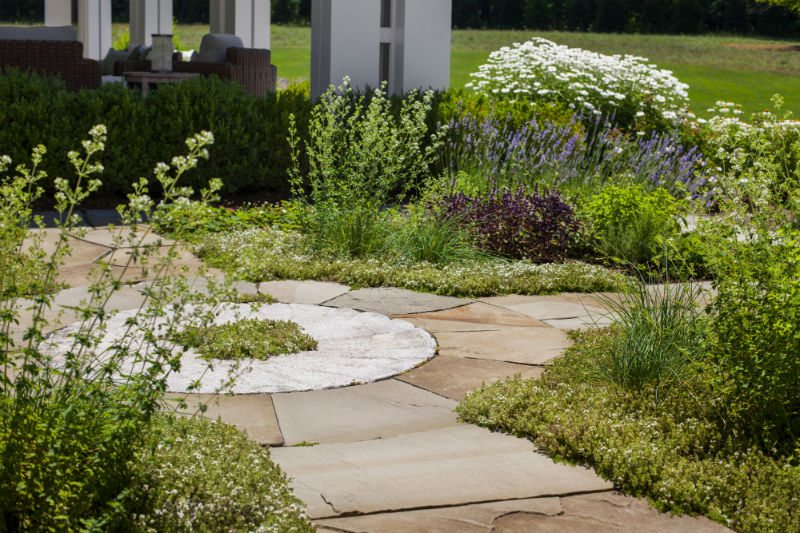This edible garden is centered around a reclaimed granite millstone with bluestone pathways connecting to the residence and other outdoor spaces. Photography by Anthony Crisafulli