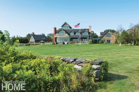 """Along the home's back side, an emerald lawn— """"the site of many a football game,"""" says the wife—unfolds to the water."""
