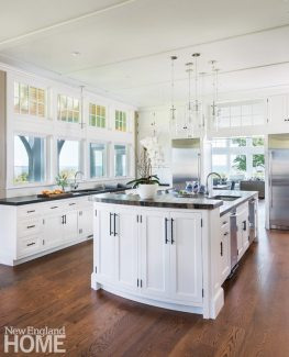 In the kitchen, a simple batten detail enhances the ceiling, transom windows welcome natural light, and myriad cabinets offer bountiful storage.