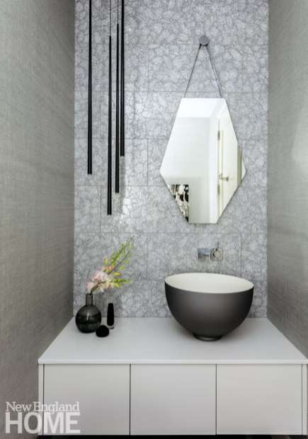 """Elms likes to create powder rooms that are an experience, she says, """"so knowing my client's love for a little glitz, we found this silvery crackle-sparkle tile that runs the wet wall."""""""