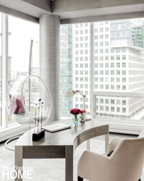 A curved desk and Lucite bubble chair are clever foils for the square frame of the office.
