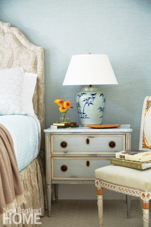 A marble-topped nightstand flanks a bed upholstered in a Schumacher paisley.