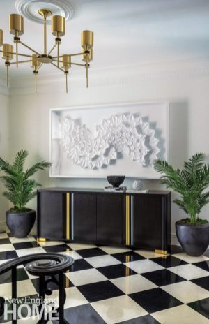 A paper sculpture by Matthew Shlian hangs above a console by Holly Hunt.