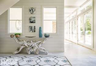 The materials used on the first floor are light, bright, and beachy, from the long, thin porcelain floor tiles to the shiplap walls and interior windows that give the entryway its casual, welcoming vibe. A bleached driftwood table with a Lucite top adds drama.