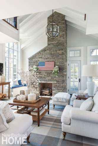 A cut-slate fireplace rises past a second-floor balcony in the family room, its horizontal ashlar pattern catching sunlight from an adjacent window.