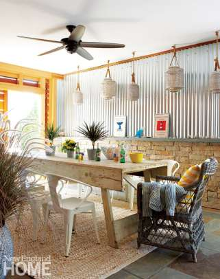 With the barn doors open, there's a view of blue water for every meal; come nightfall, the galvanized steel wall will enhance the glow from an array of lanterns.