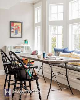The large window in the kitchen's dining area fills the kitchen with light. An upholstered banquette is paired with classic Windsor-style chairs and vintage table to create a relaxed family gathering space.
