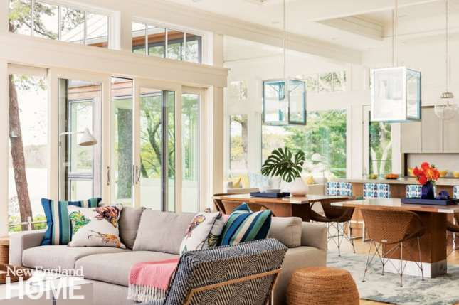 """The dining tables sit between the living room and kitchen in the home's central """"life space,"""" with a glass-enclosed sitting room projecting toward the backyard."""