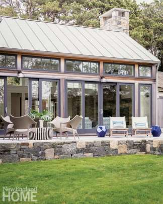 A wall of windows looks out on the rear patio sprinkled with an array of comfortable outdoor furniture.