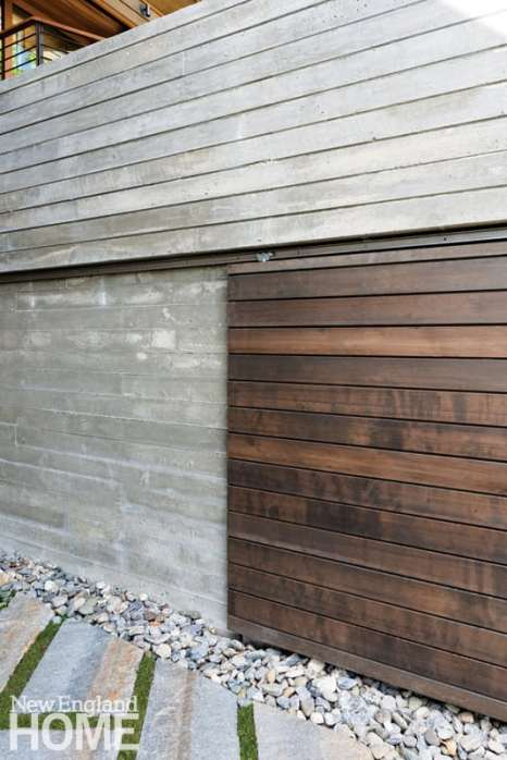 A sliding wood door in the concrete retaining wall beneath the outside stairs conceals a generous storage area.